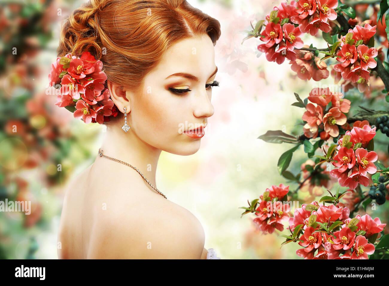 La relaxation. Profil de la beauté des cheveux rouge sur fond de fleurs naturelles. La nature. Blossom Banque D'Images
