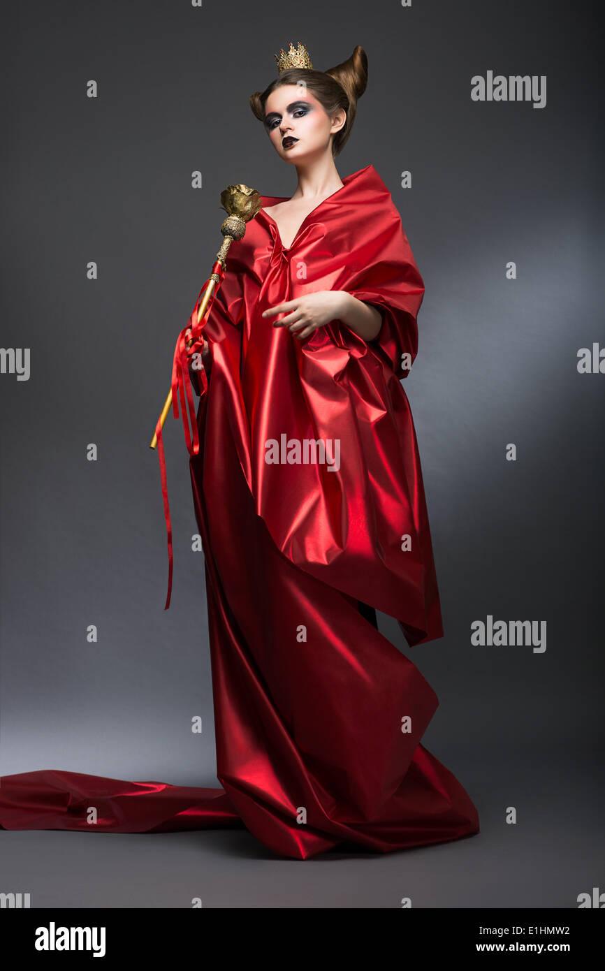 Moyen-Âge. La magie. Femme en rouge l'Assistant divin Pallium avec sceptre. La sorcellerie Photo Stock