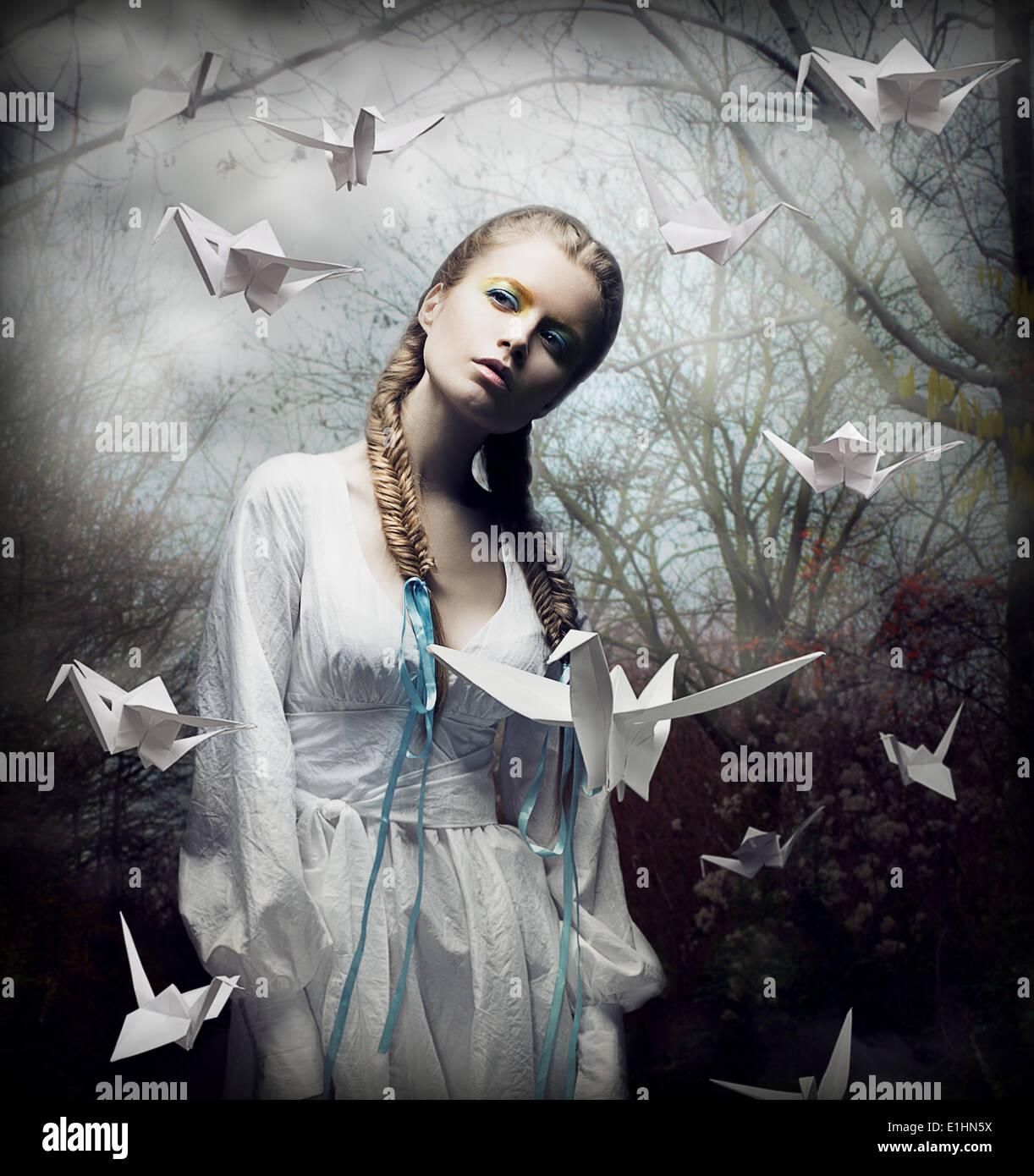 L'imagination. Blonde romantique avec l'Origami planant dans les oiseaux de la forêt Spooky. Magic Photo Stock