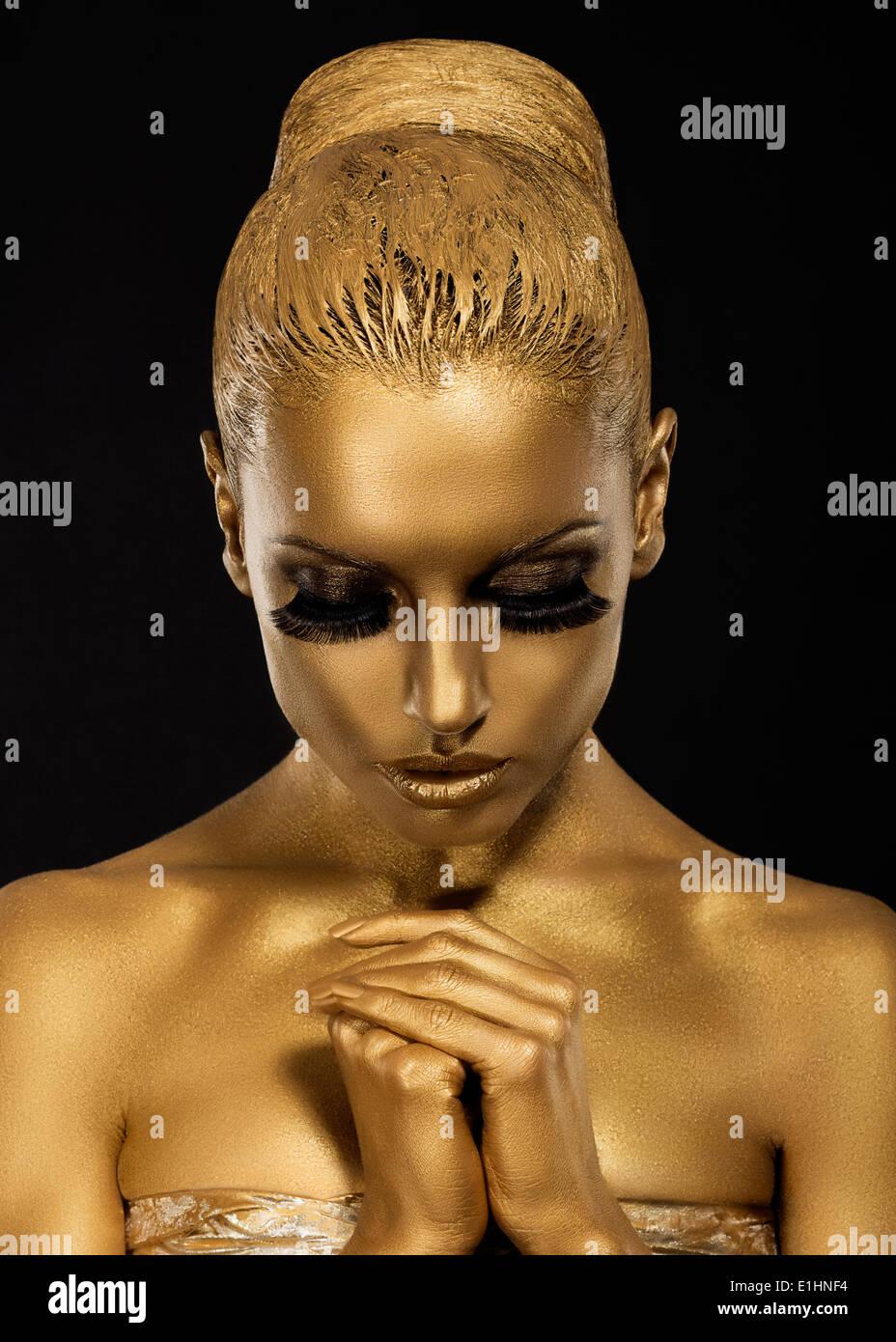 La conviction. Femme de style traditionnel avec des mains qui prient. Maquillage d'or Photo Stock