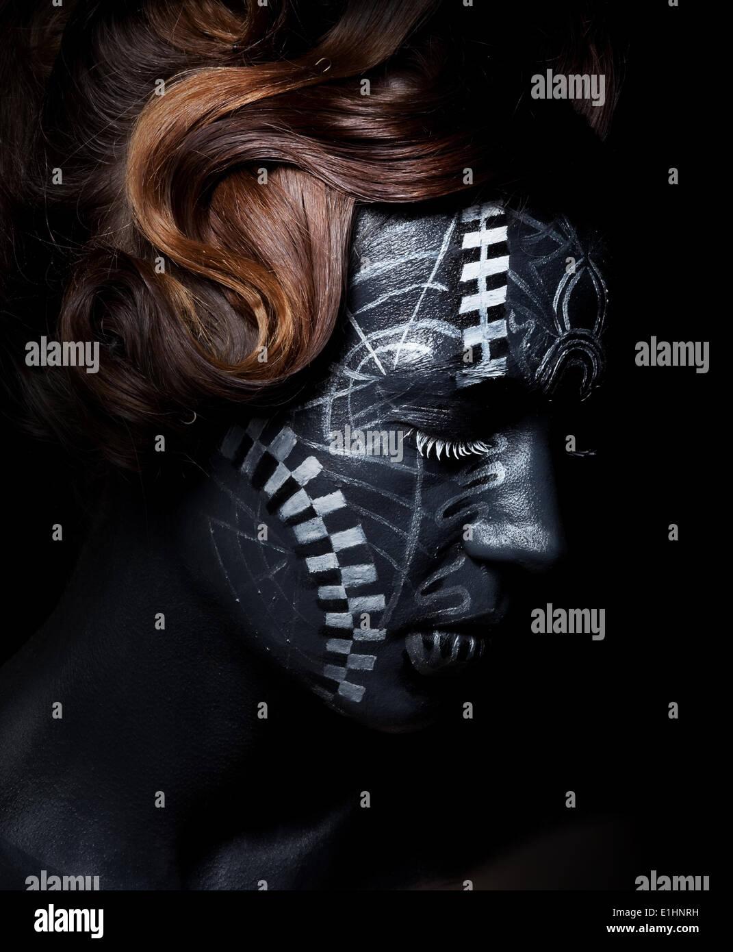Femme triste visage peint en noir avec un masque de carnaval Photo Stock