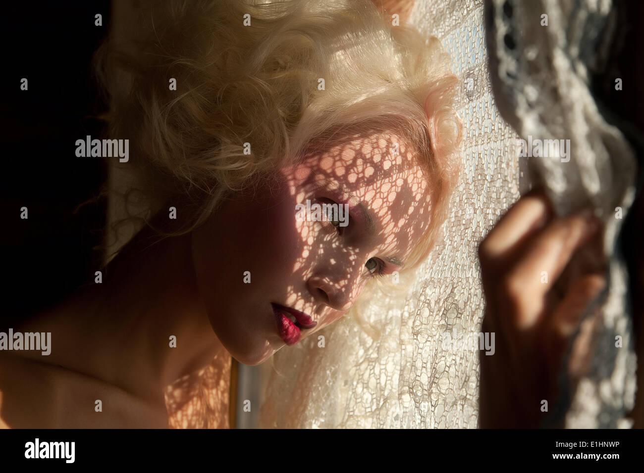 Belle blonde jeune fille à la recherche par la fenêtre Photo Stock