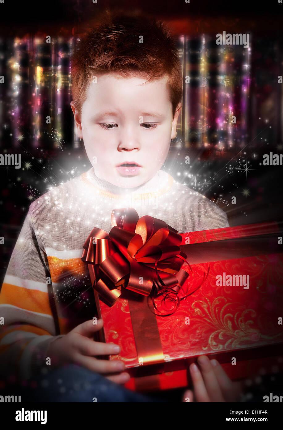 Anniversaire - belle peu excité cheveux rouge enfant regardant heureusement en boîte rouge - cadeau anniversaire Photo Stock