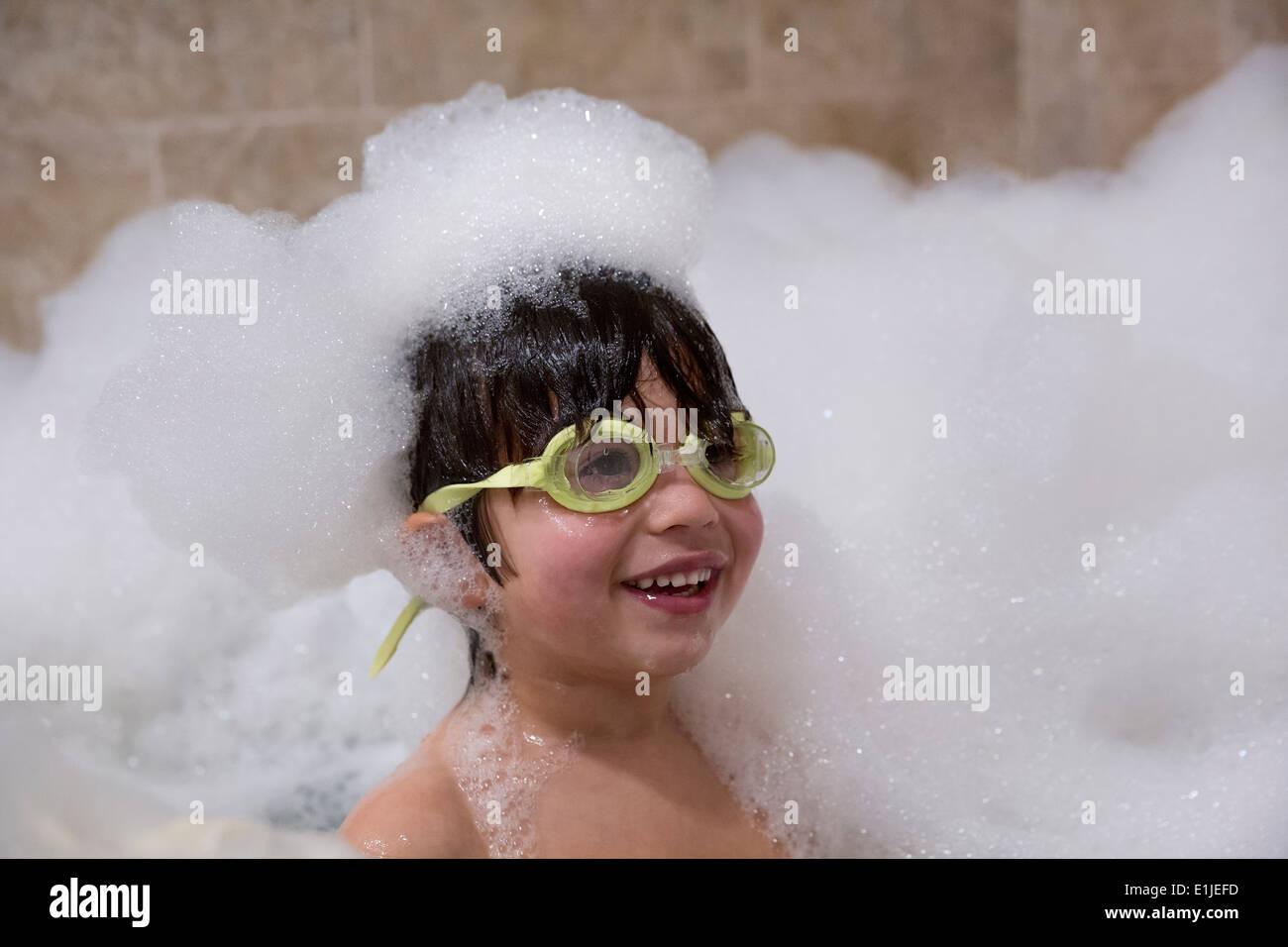 Portrait de jeune garçon portant ces lunettes in bubble bath Banque D'Images