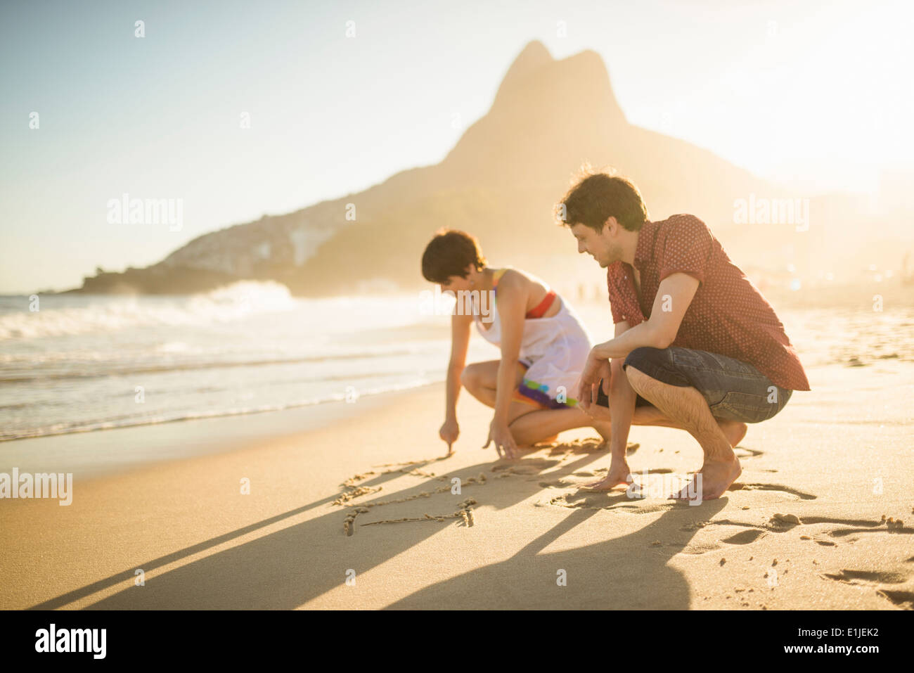 Jeune couple écrit sur le sable, Ipanema Beach, Rio, Brazil Photo Stock