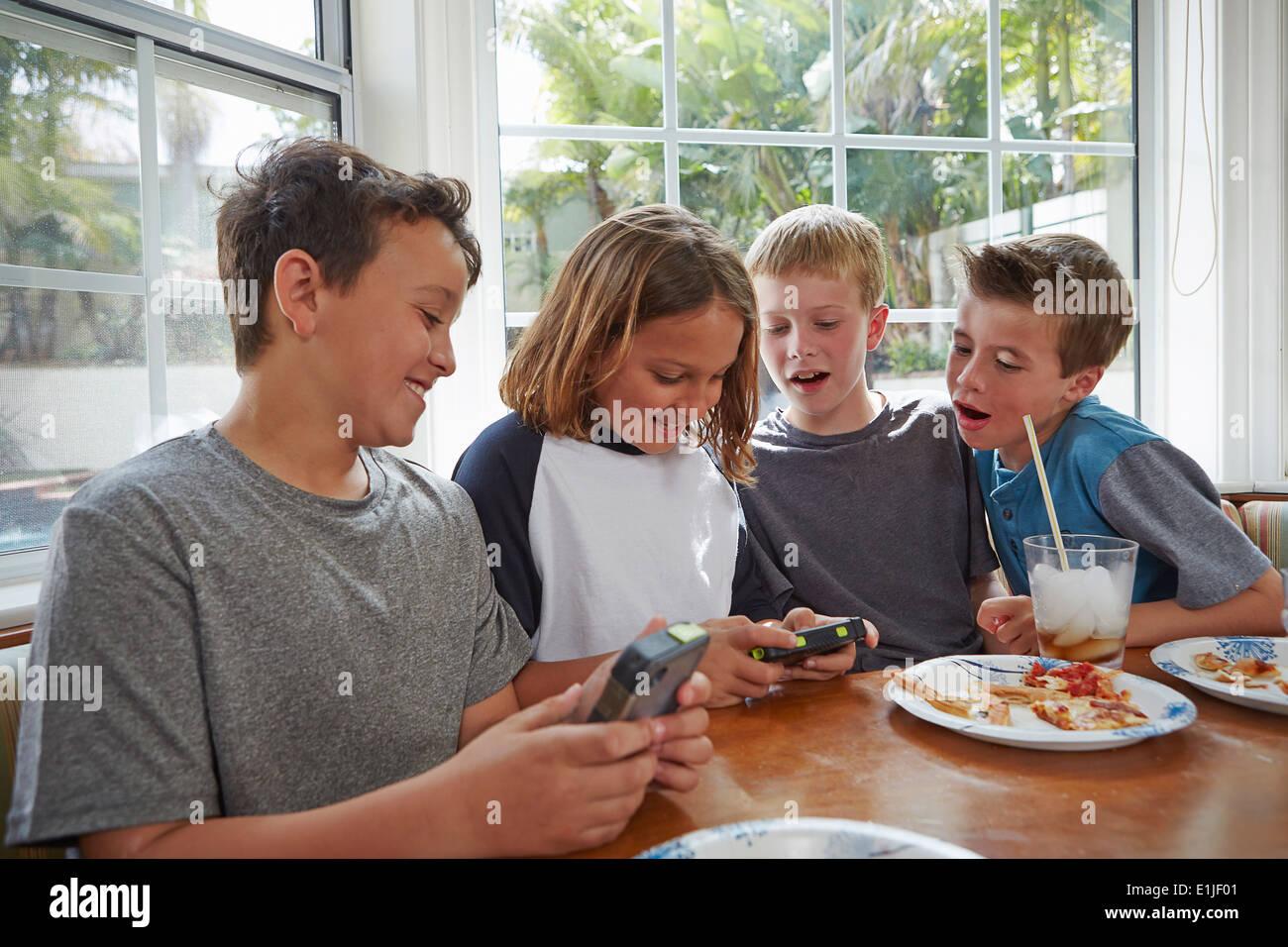 Des garçons jouent à des jeux vidéo de poche Photo Stock