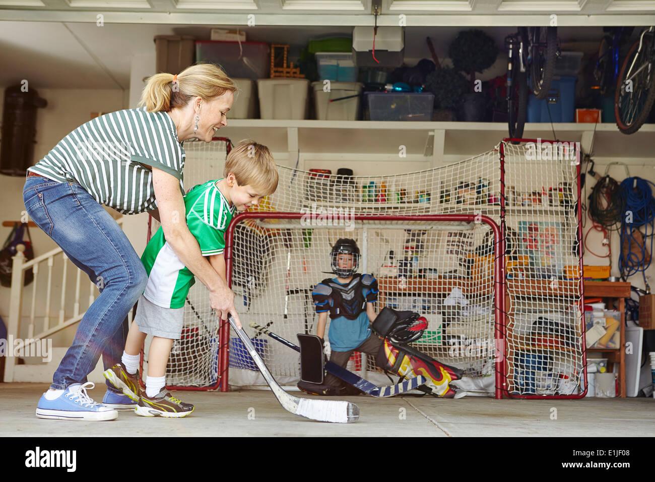 Mère jouant au hockey en garage, deux fils Photo Stock