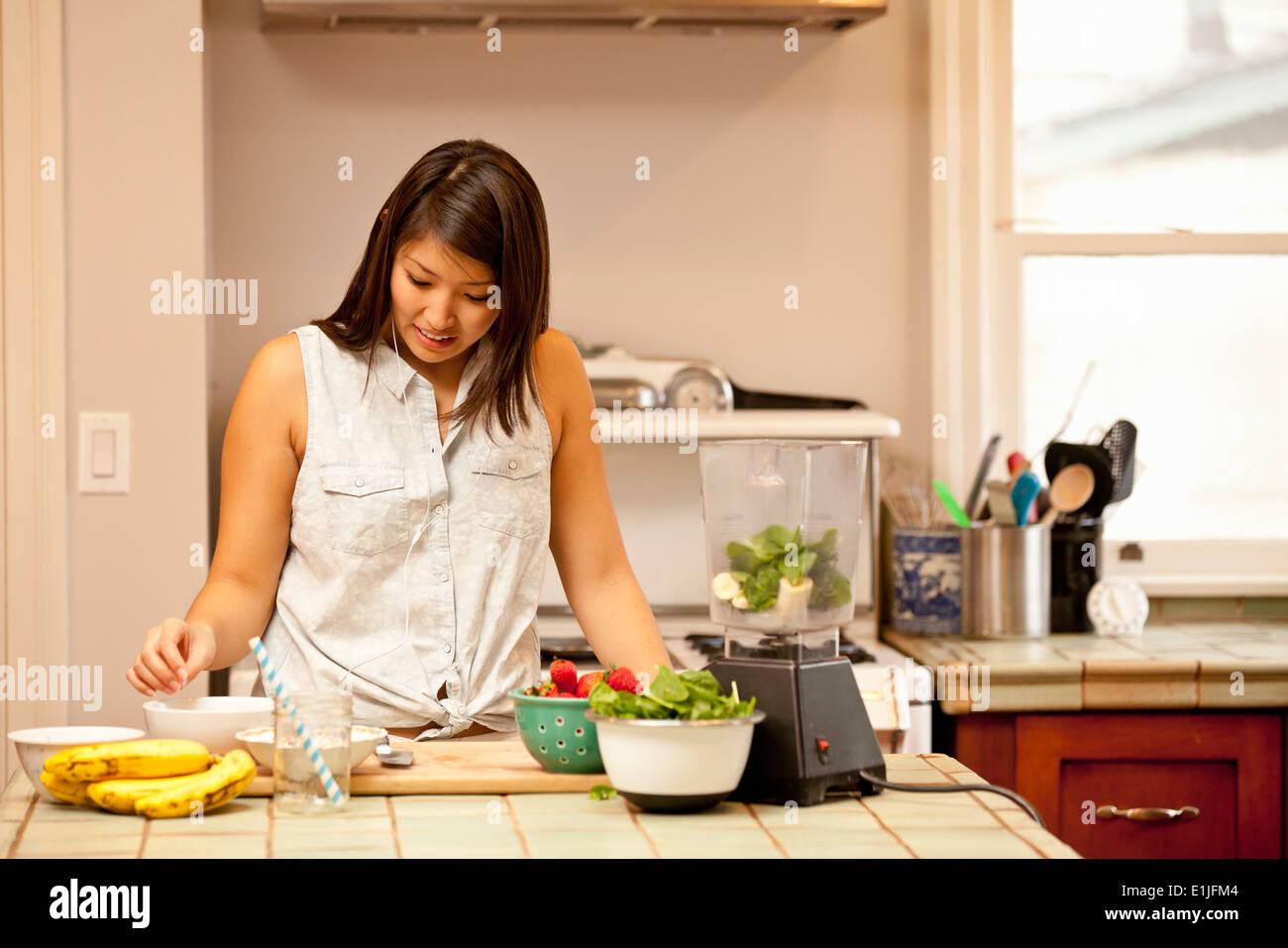 Jeune femme faisant smoothie vert dans la cuisine Photo Stock