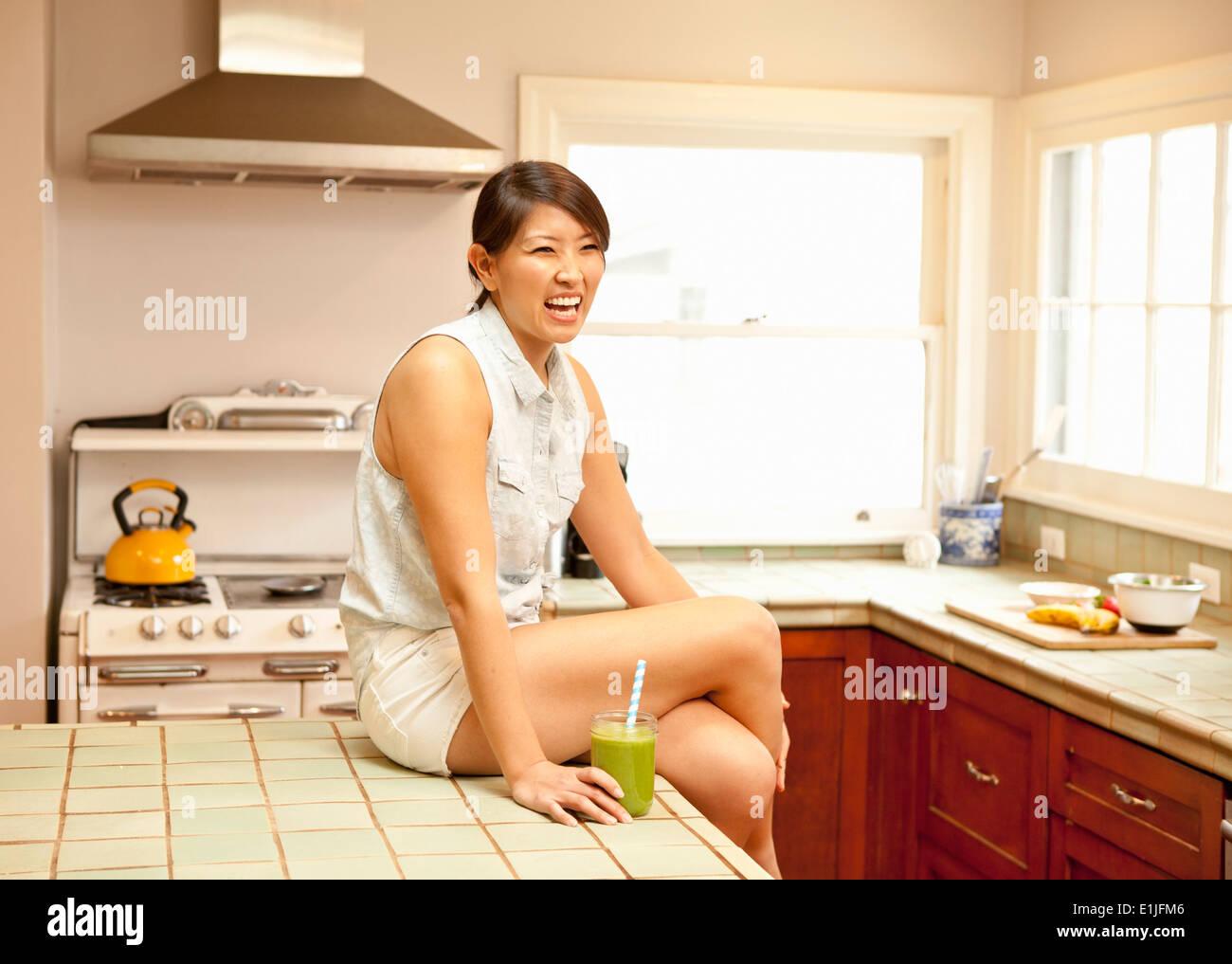 Jeune femme avec smoothie vert dans la cuisine Photo Stock