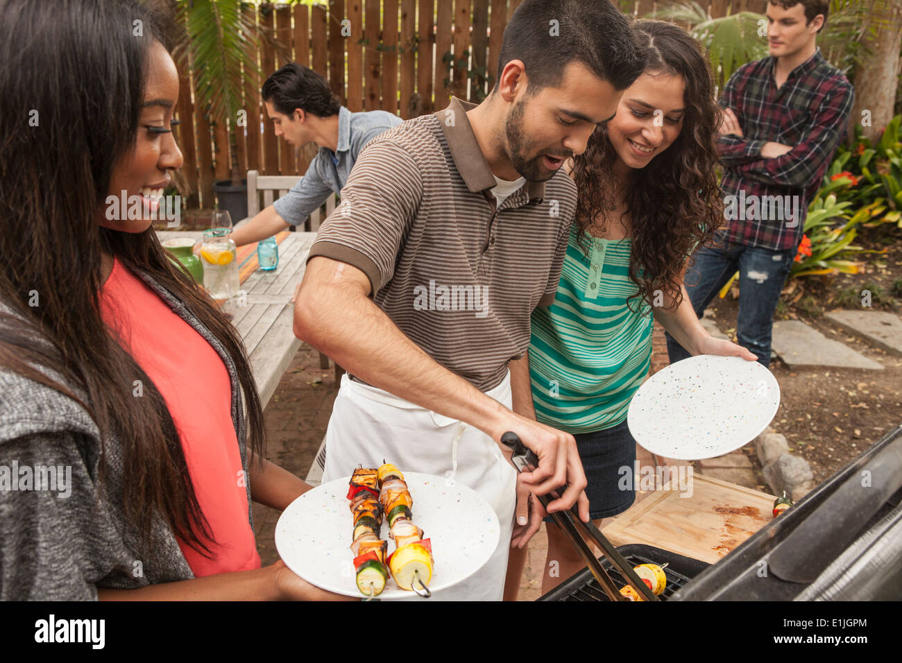 Amis assis autour de la table barbecue partage Photo Stock