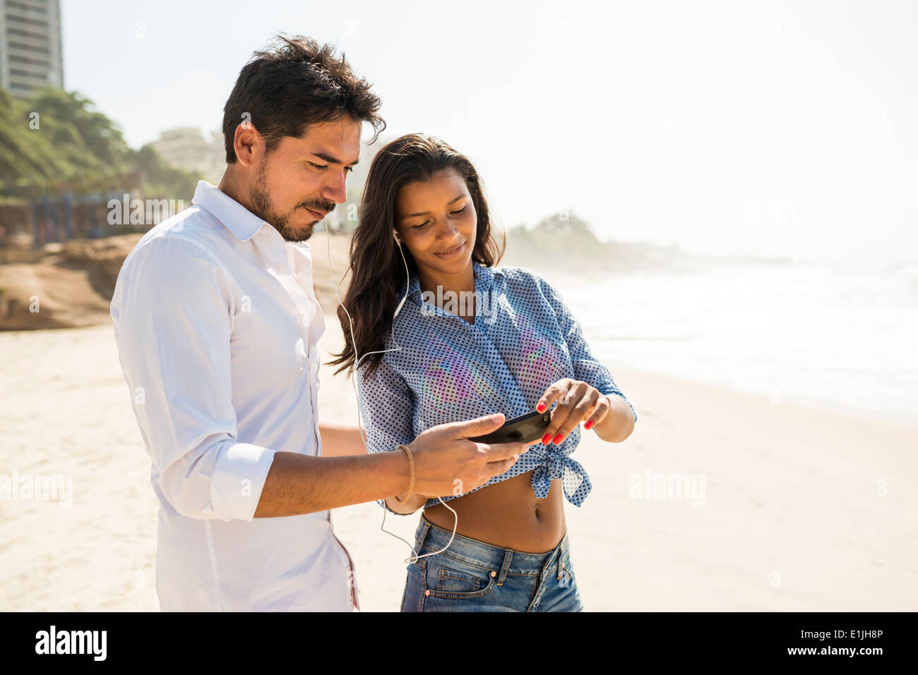 Couple de la musique à partir de smartphone, Arpoador beach, Rio de Janeiro, Brésil Photo Stock