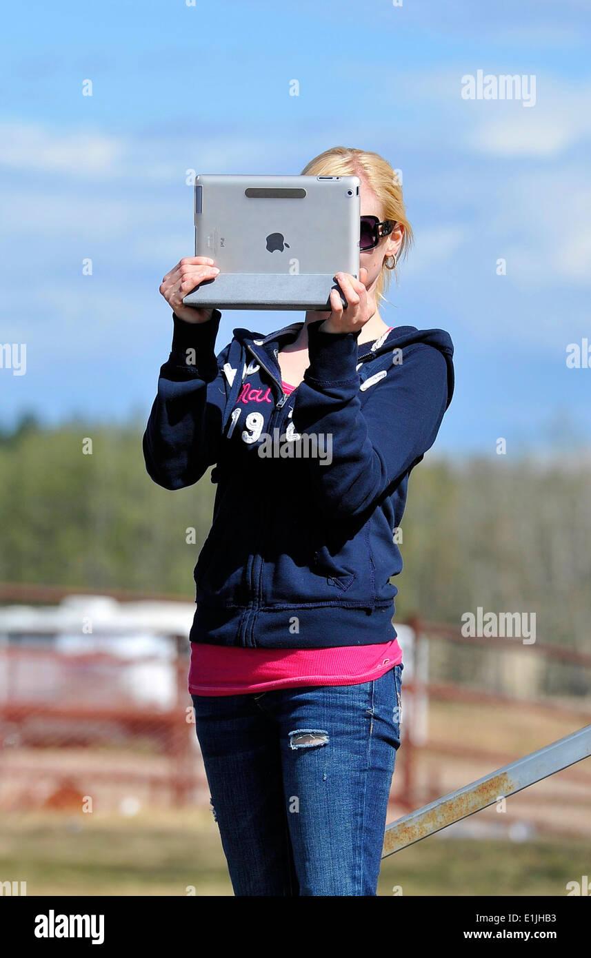 Une jeune femme à l'aide d'un ipad pour prendre une photo Photo Stock