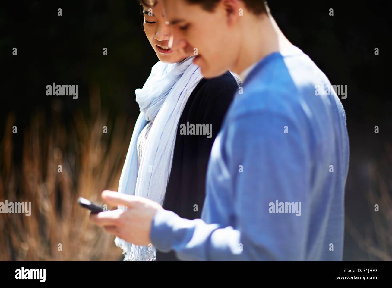 Jeune couple, man using cell phone Photo Stock