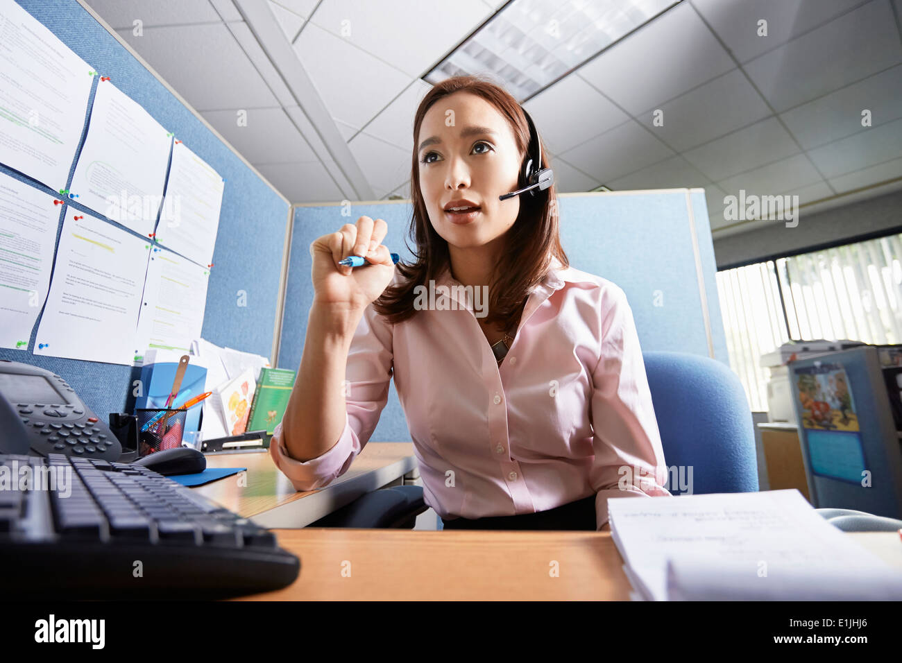 Young female office worker talking on headset in office Photo Stock