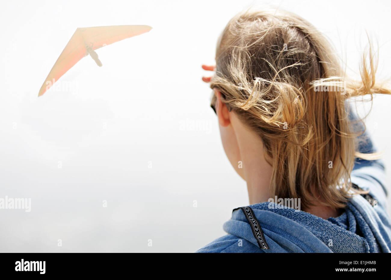 Femme regardant planeur dans le ciel Photo Stock