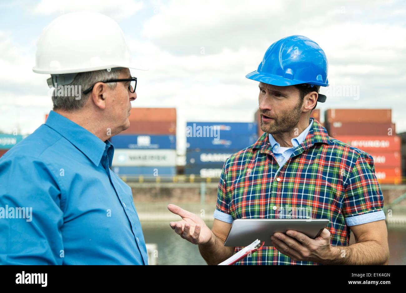 Deux hommes avec des casques de sécurité parler au port à conteneurs Photo Stock