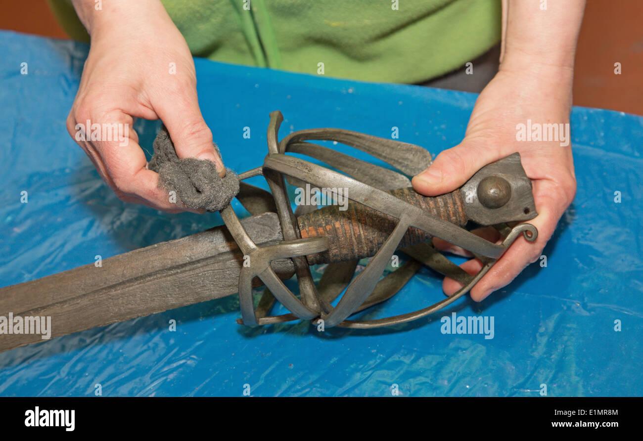 Restauration de old sword - Détail de la main au travail Photo Stock