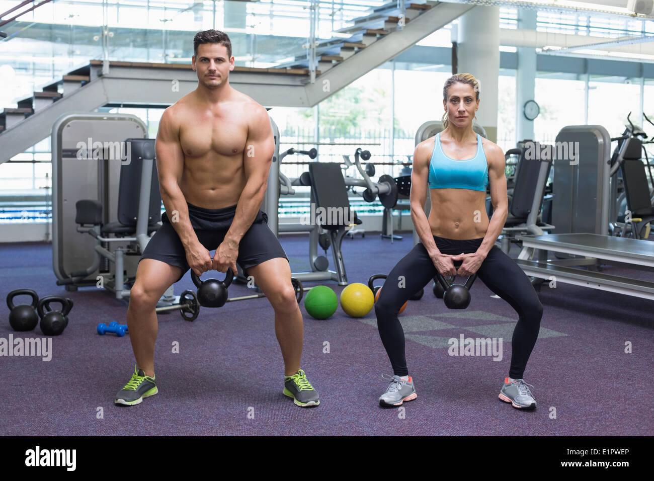 L'homme et la femme musculation kettlebells de levage dans un squat Photo Stock