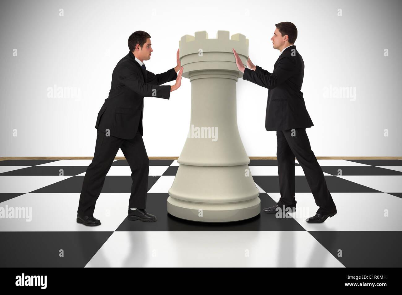 Image composite des gens d'affaires poussant chess piece Banque D'Images