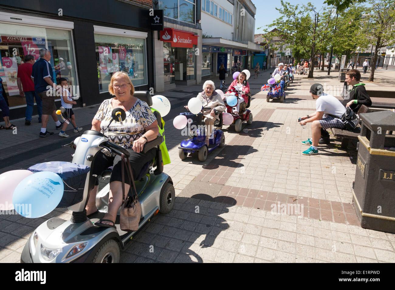 Groupe de personnes font un fun run de bienfaisance au profit de l'hôpital de Southampton décorées sur un fauteuil motorisé. Photo Stock