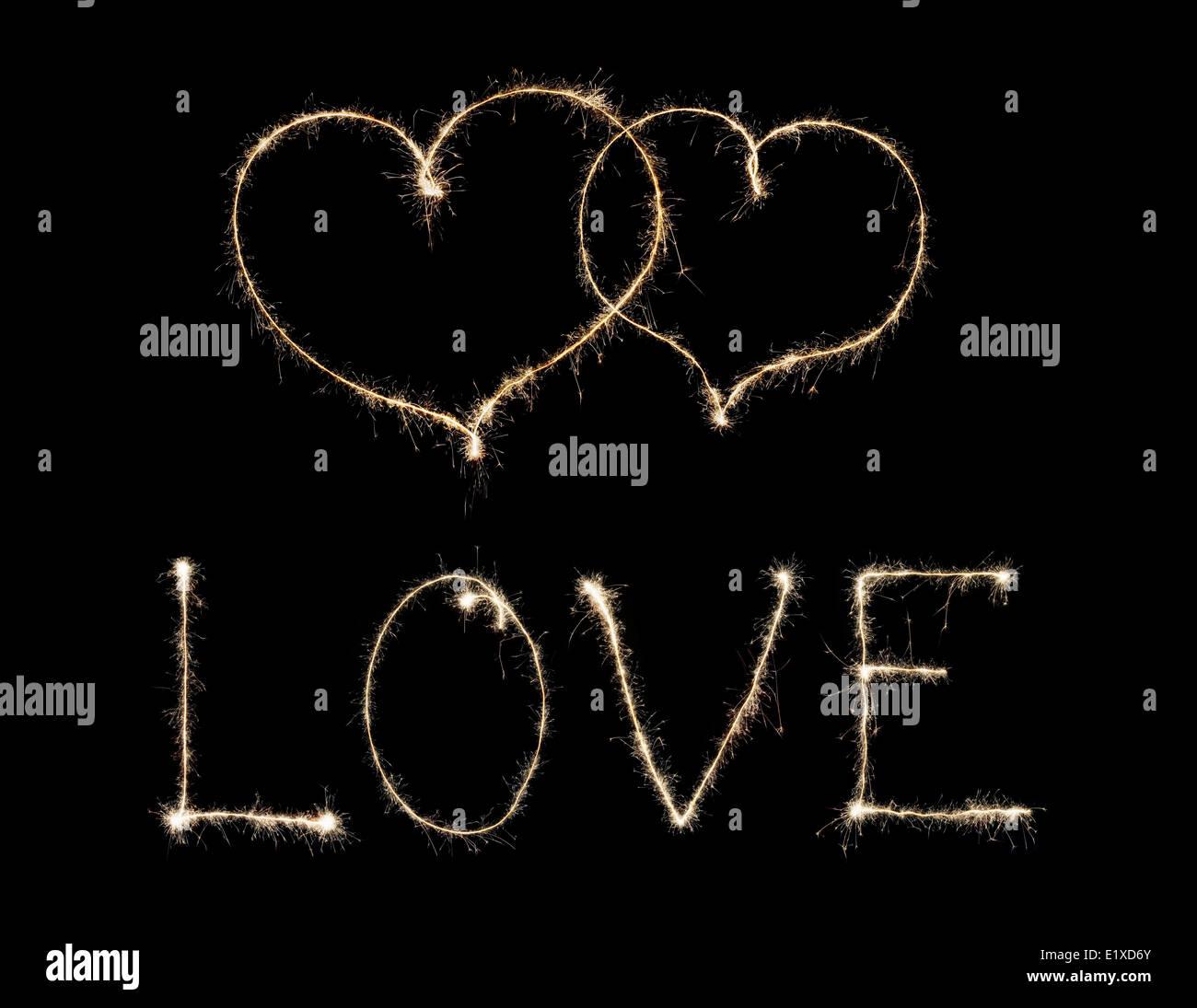 Mot amour et deux coeurs de sparkler isolé sur fond noir Banque D'Images