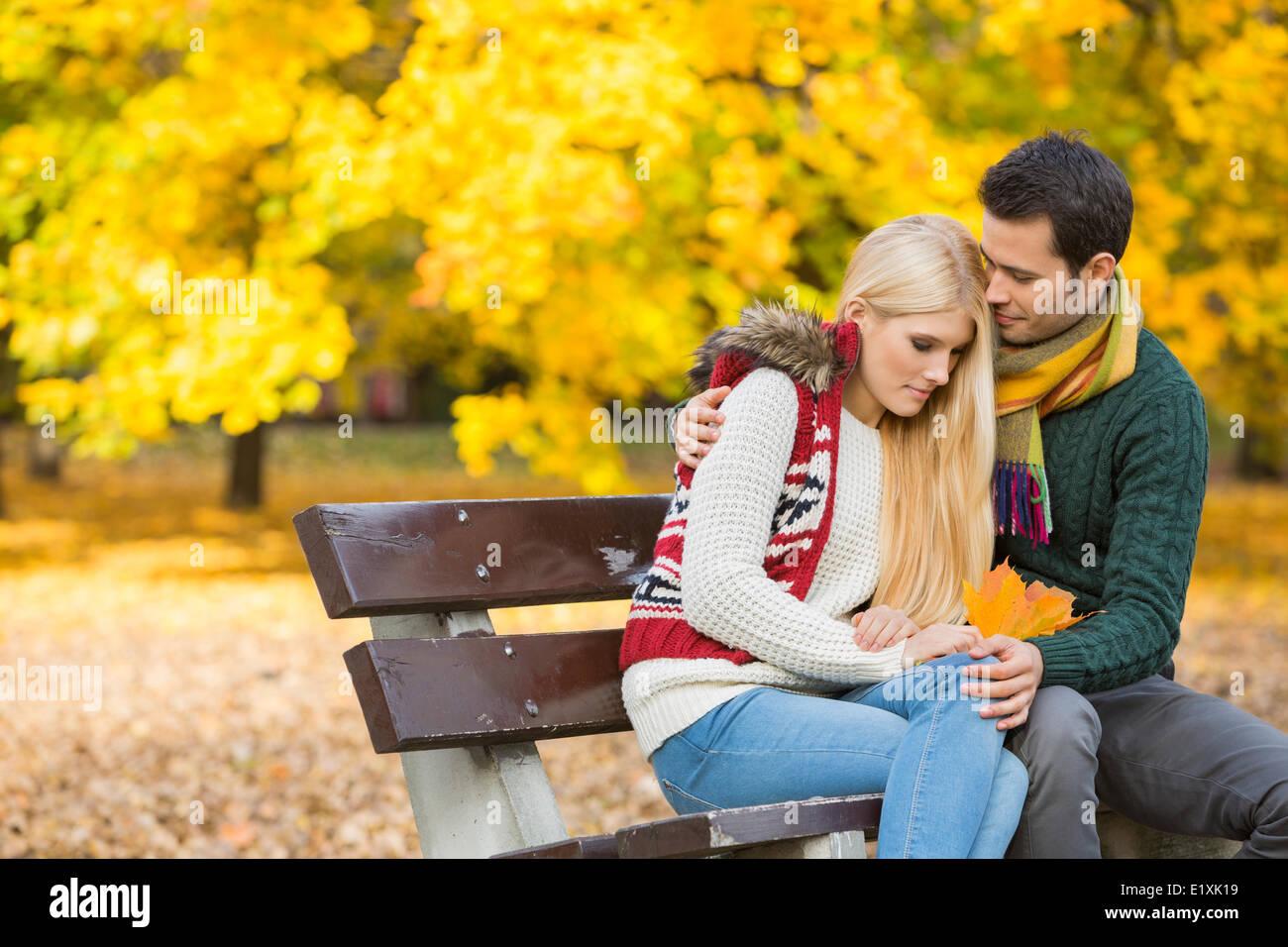Jeune homme aimant hugging femme timide sur banc de parc au cours de l'automne Photo Stock