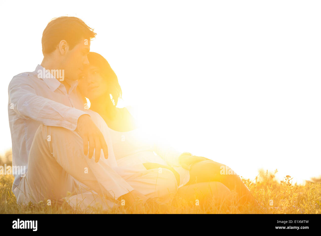 Loving young couple sitting on grass at park contre ciel clair Photo Stock