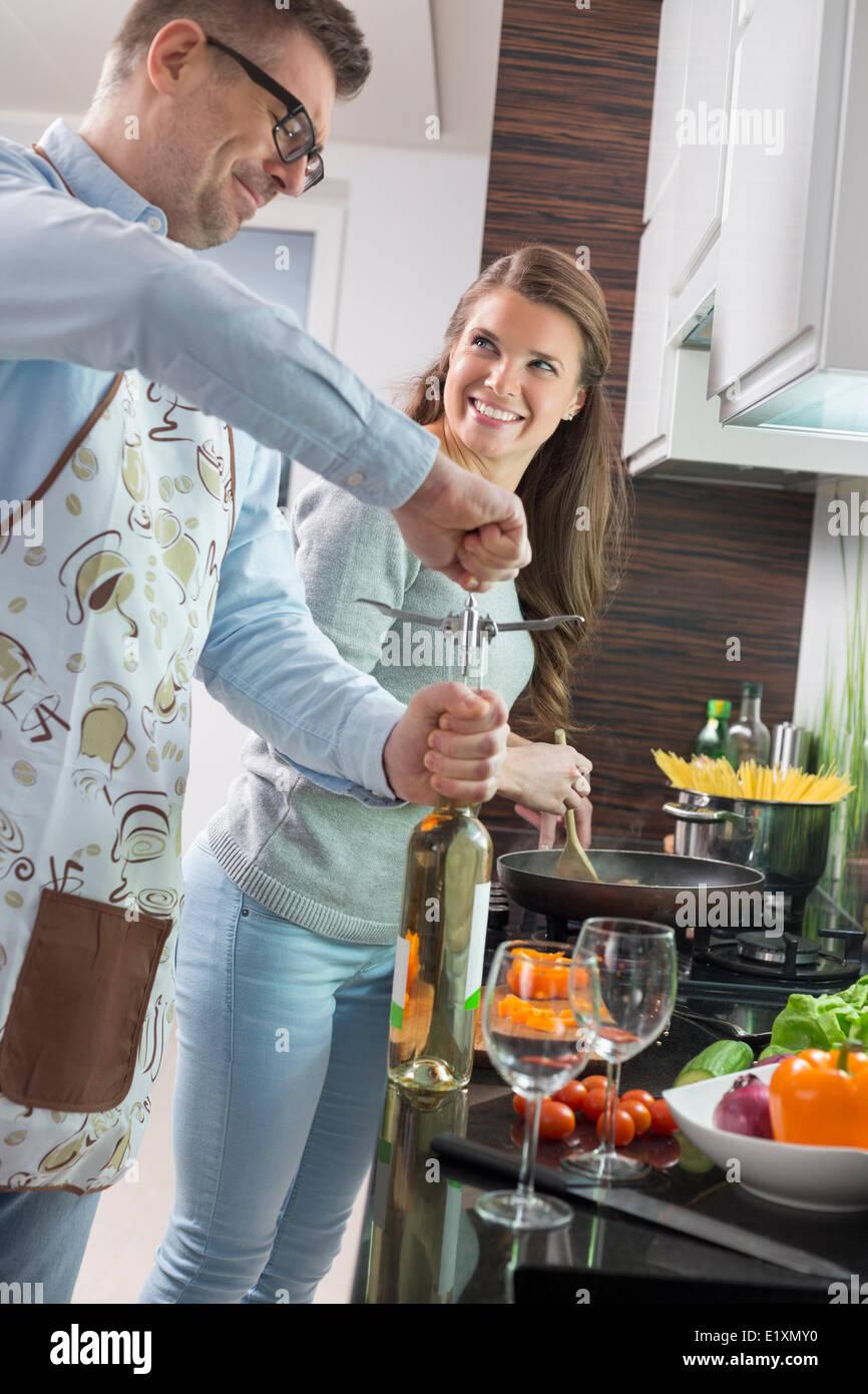 Bouteille de vin d'ouverture de l'homme pendant la cuisson avec woman in kitchen Photo Stock