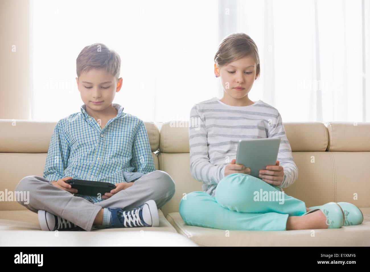 Frères et sœurs mignon en utilisant des technologies sur canapé à la maison Photo Stock