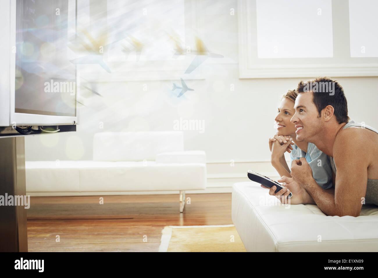 Happy young couple watching TV à la maison Photo Stock