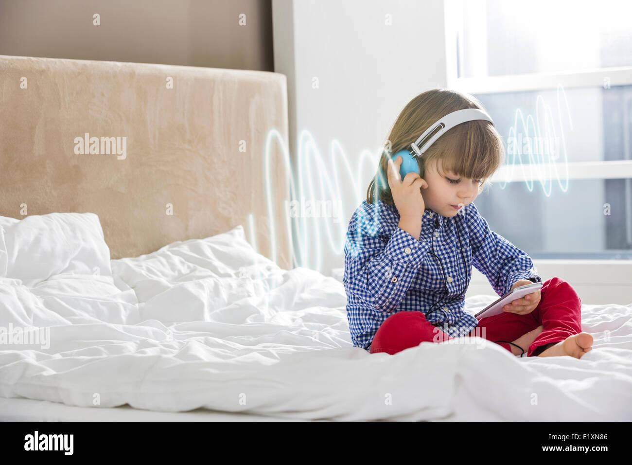 Toute la longueur de l'écoute au casque musique garçon on bed Photo Stock