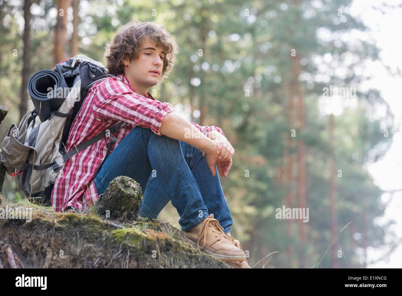 Toute la longueur de l'homme réfléchi backpacker détente sur falaise en forêt Photo Stock