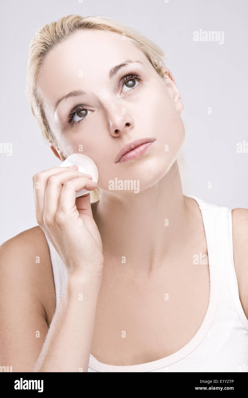 Belle blonde dépose maquillage facial Photo Stock