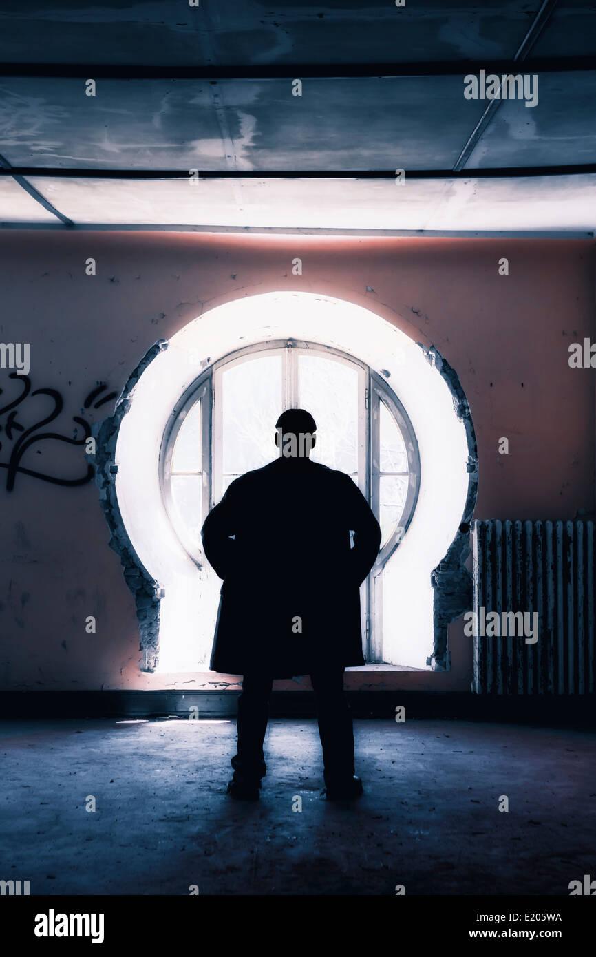 Silhouette d'un homme en face d'une fenêtre dans un vieux bâtiment abandonné Photo Stock