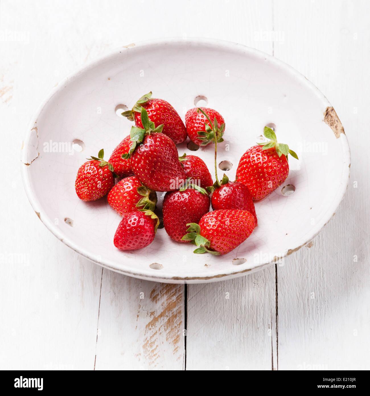 La fraise au Vintage passoire en céramique blanche sur fond de bois Photo Stock