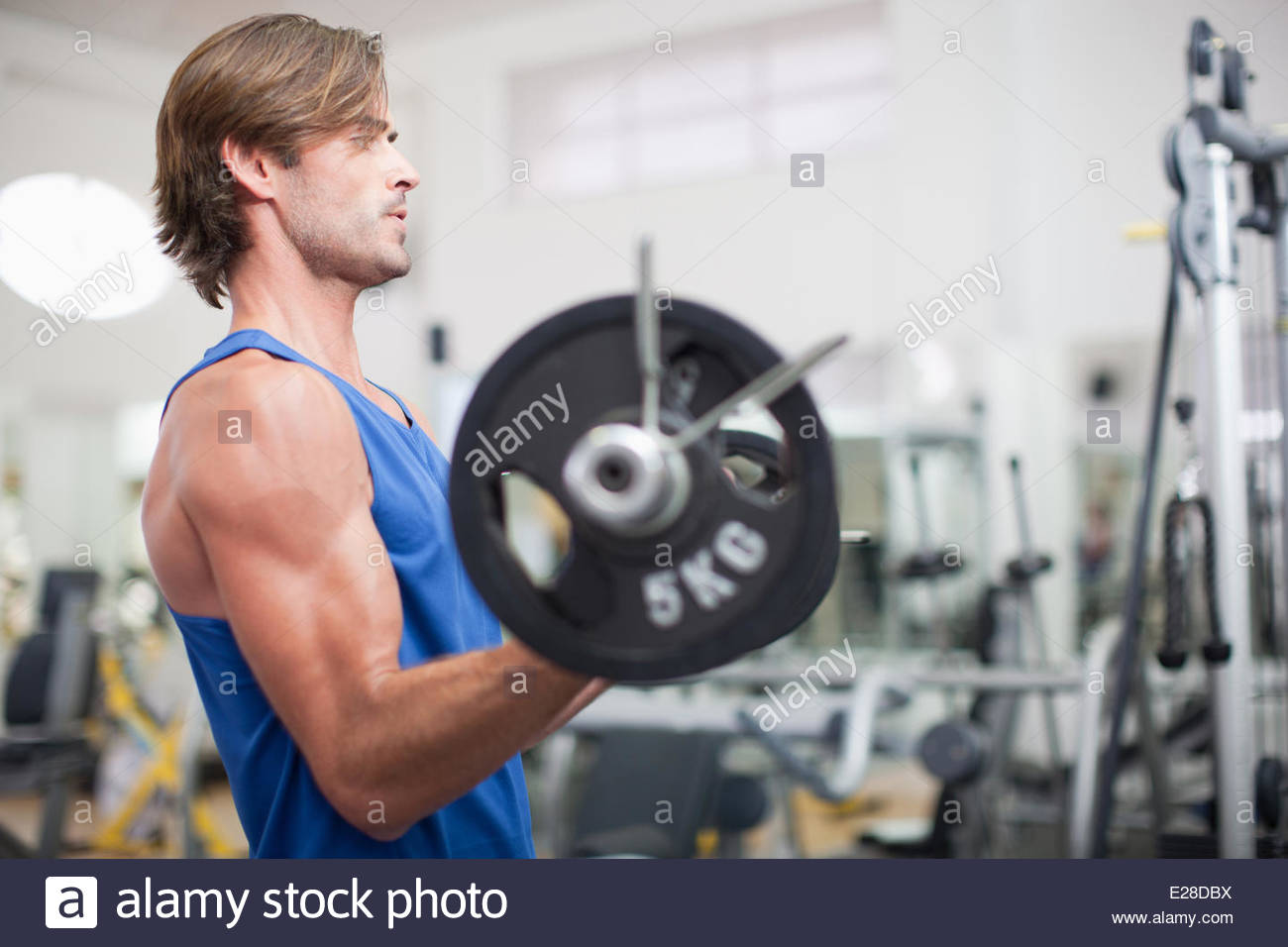 Man lifting barbell in gymnasium Photo Stock