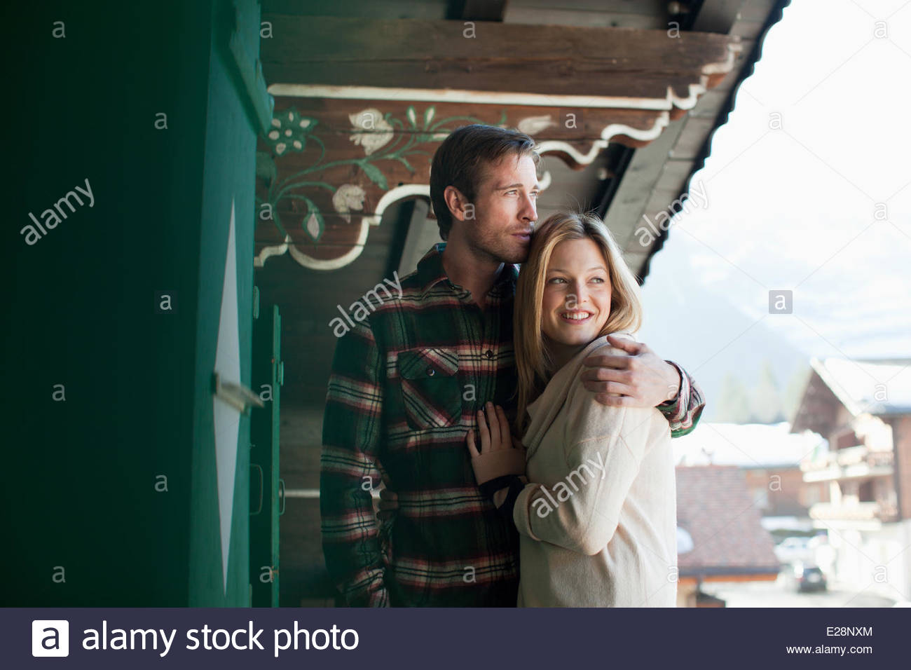 Smiling couple hugging on cabin porch Photo Stock