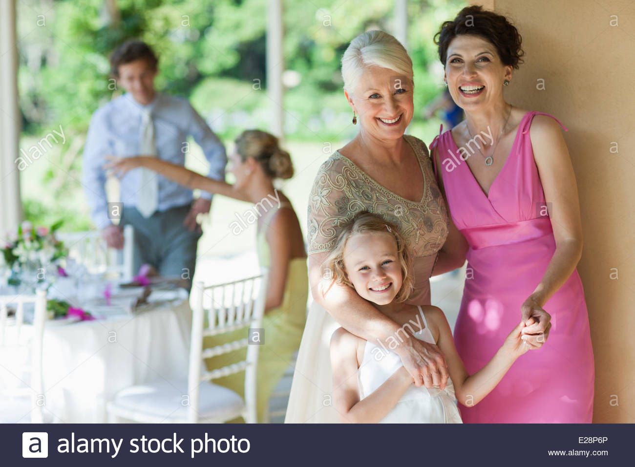 Family holding hands at wedding reception Photo Stock