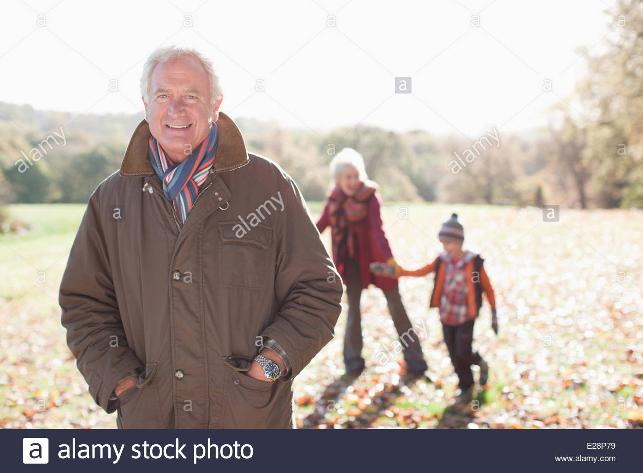 Les grands-parents playing in park with grandson Photo Stock