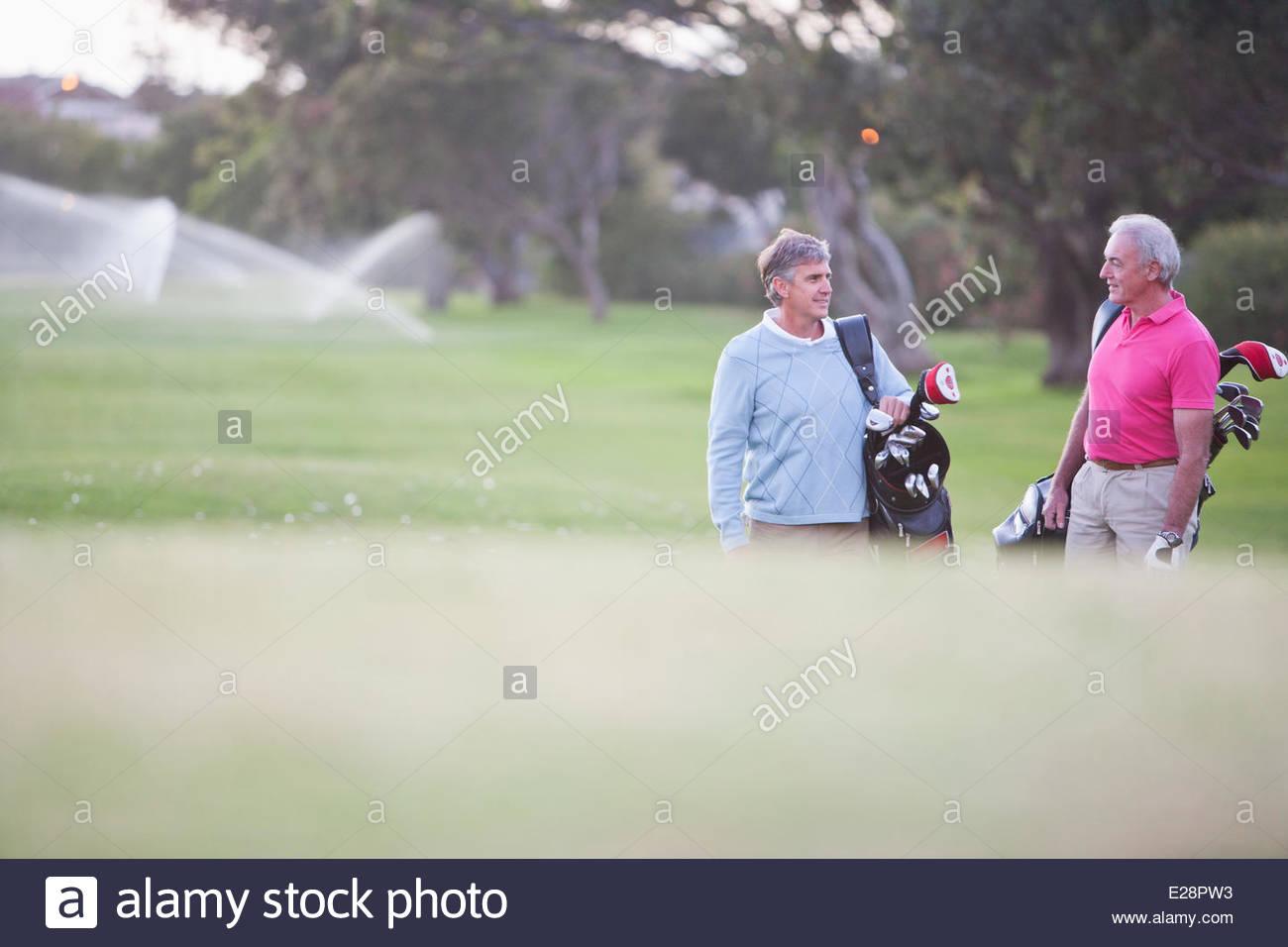 Les hommes tirant des voiturettes de golf Photo Stock