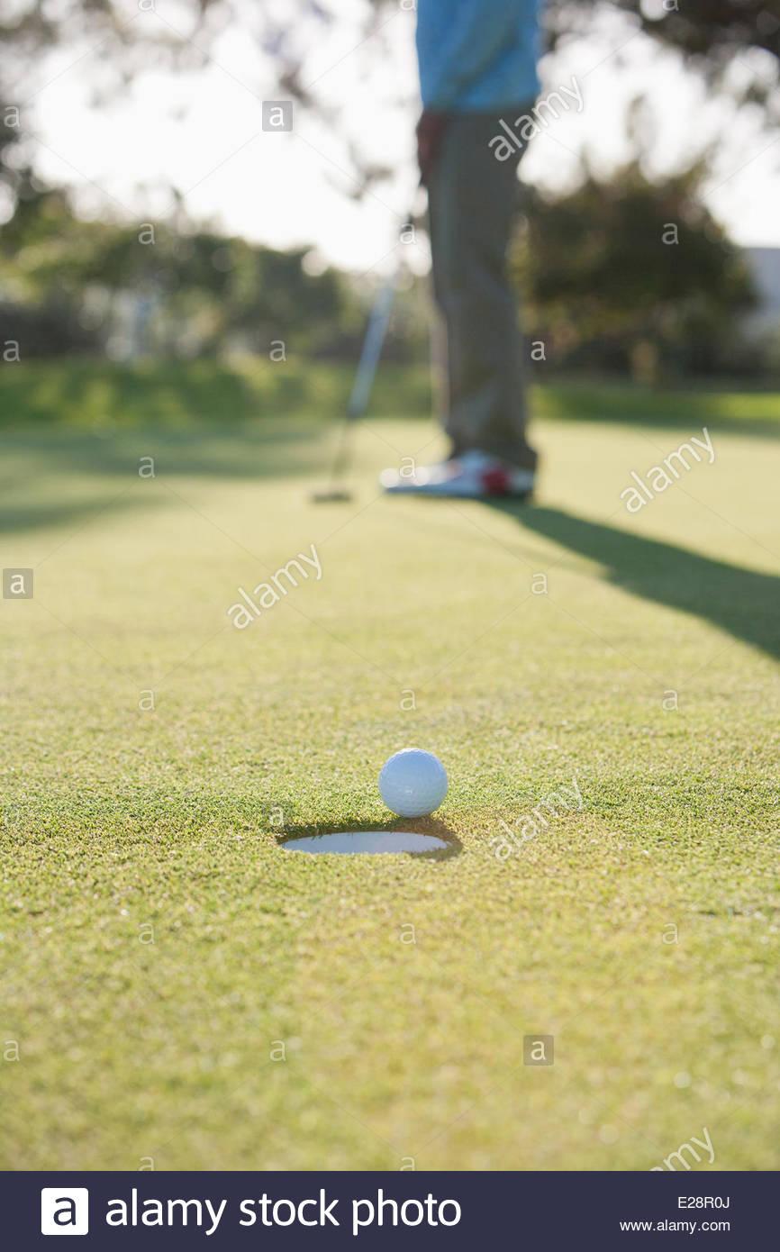 L'homme s'enfoncer dans le trou de balle de golf Photo Stock