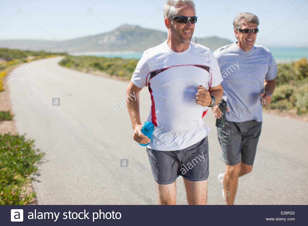 Les hommes le jogging et au transport de l'eau bouteilles Photo Stock