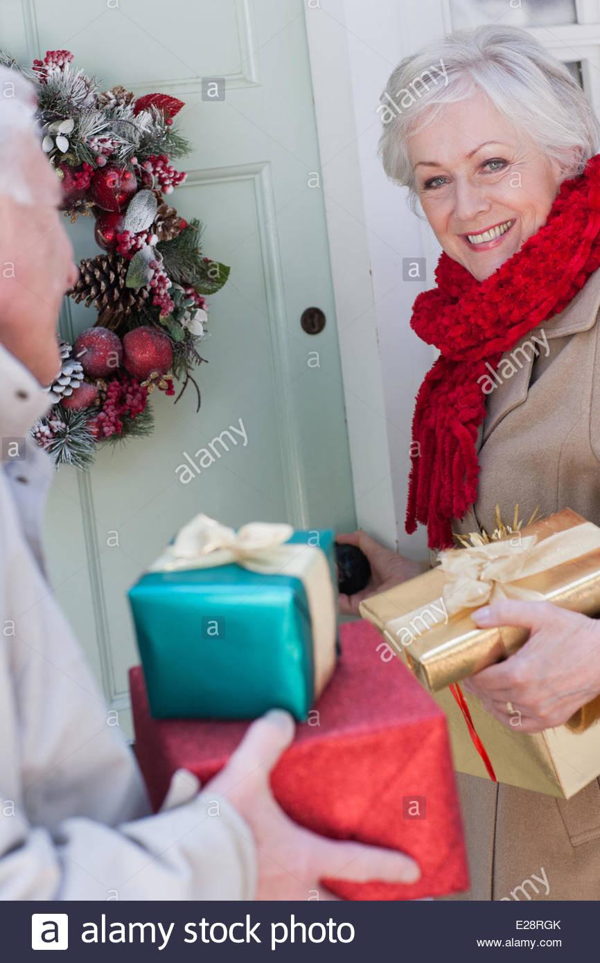 Couple avec cadeaux de Noël debout à la porte Photo Stock