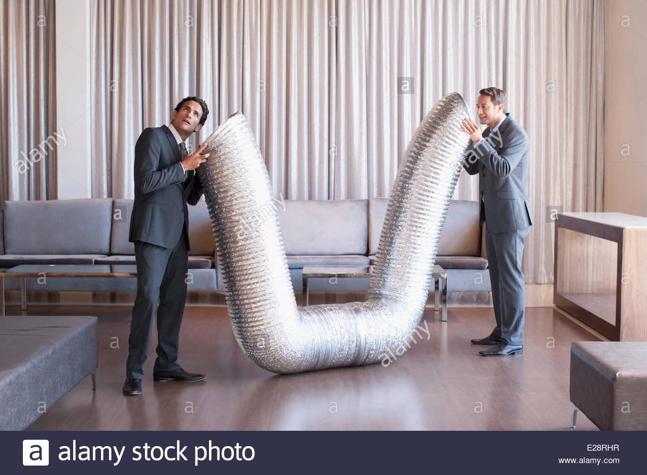 Business people holding tuyau métallique dans le hall de l'hôtel Photo Stock