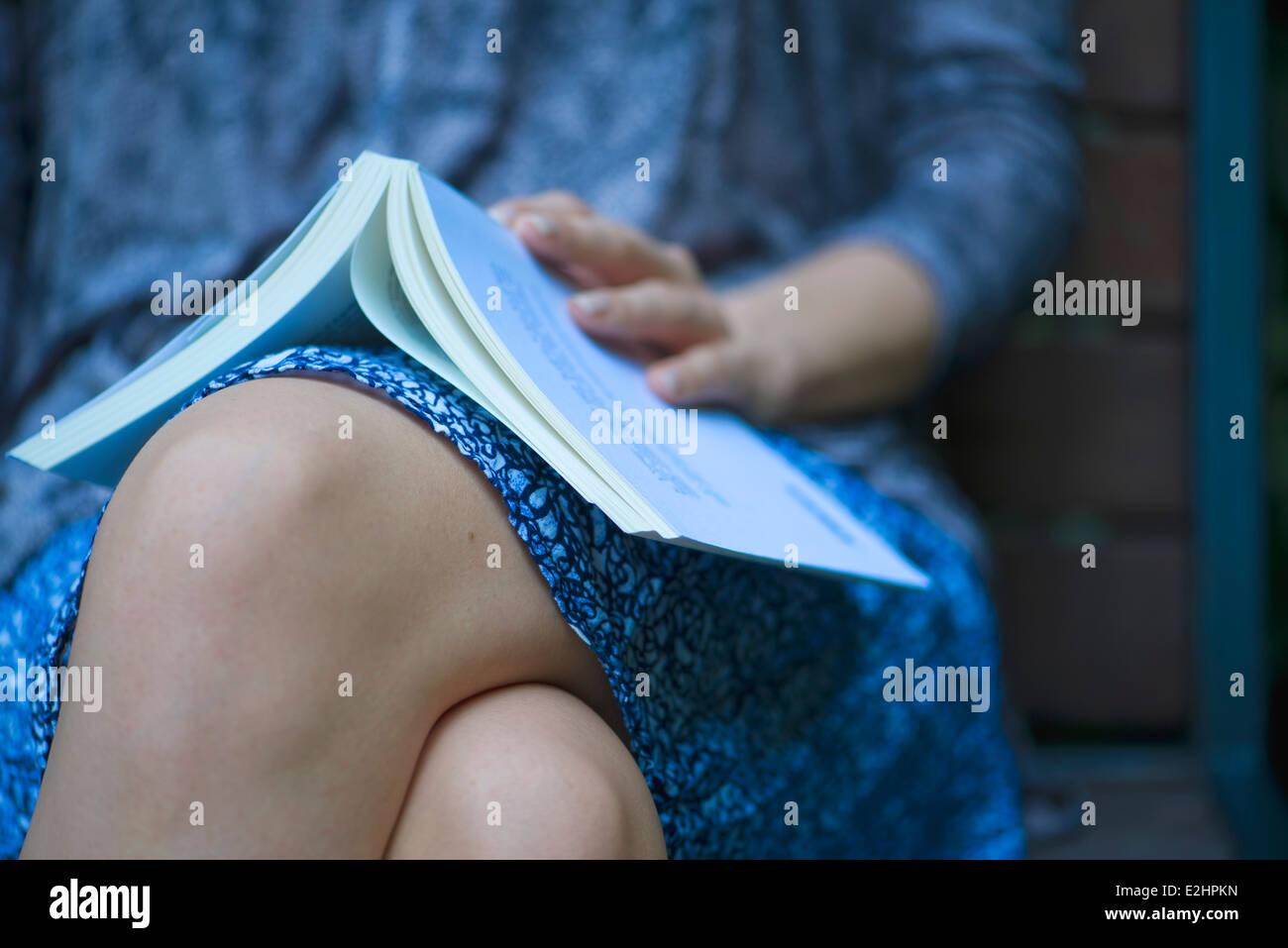 Femme assise avec livre ouvert reposant sur les genoux, cropped Photo Stock