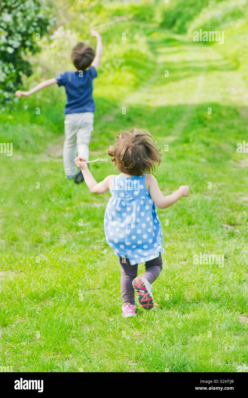 Les enfants courent sur le chemin dans la campagne Photo Stock