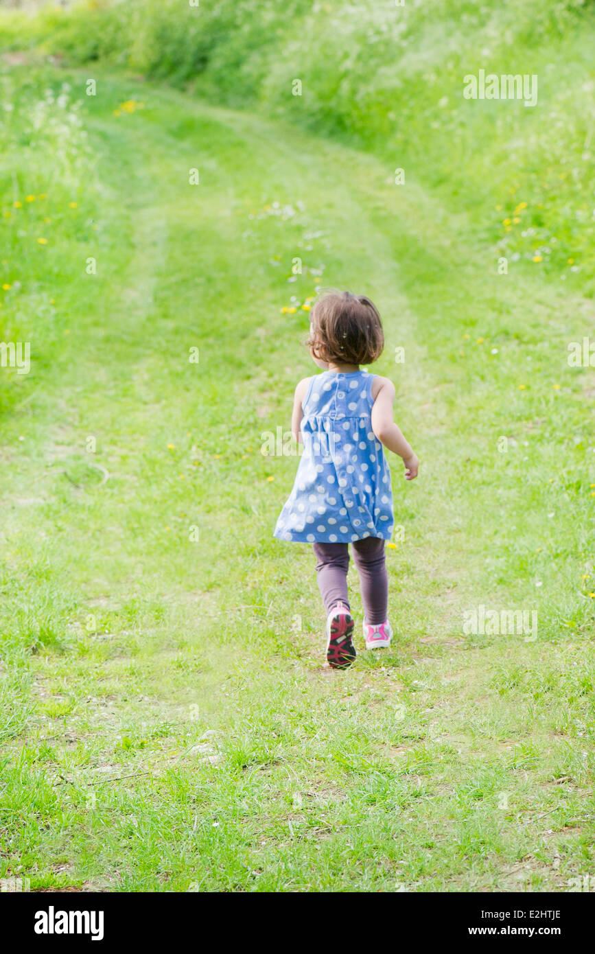 Petite fille s'exécutant sur chemin à travers campagne, vue arrière Photo Stock
