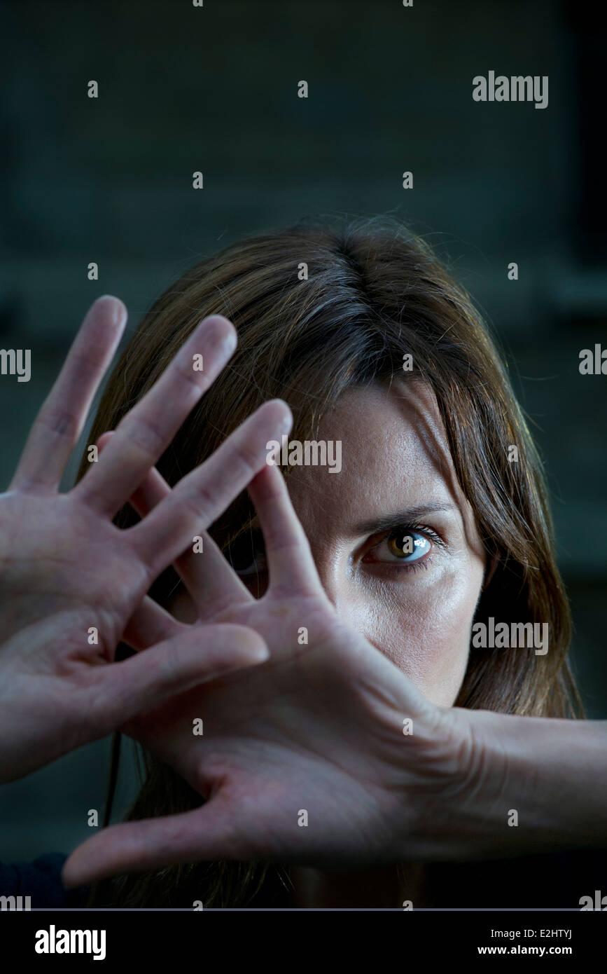 Woman raising hands pour parer à l'attaque Banque D'Images