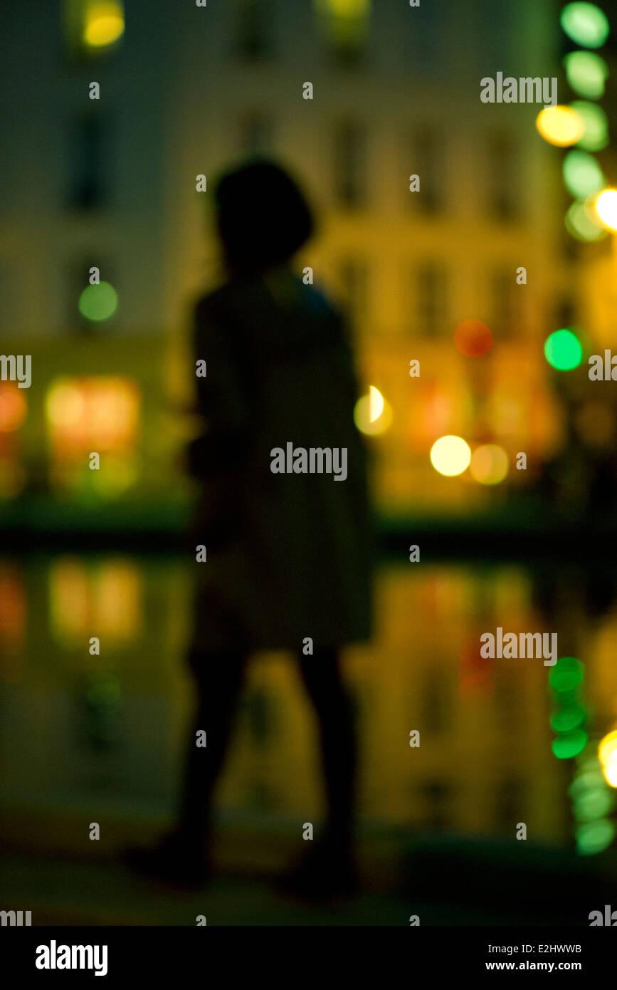 Femme marcher la nuit le long de la rivière urbaine Photo Stock