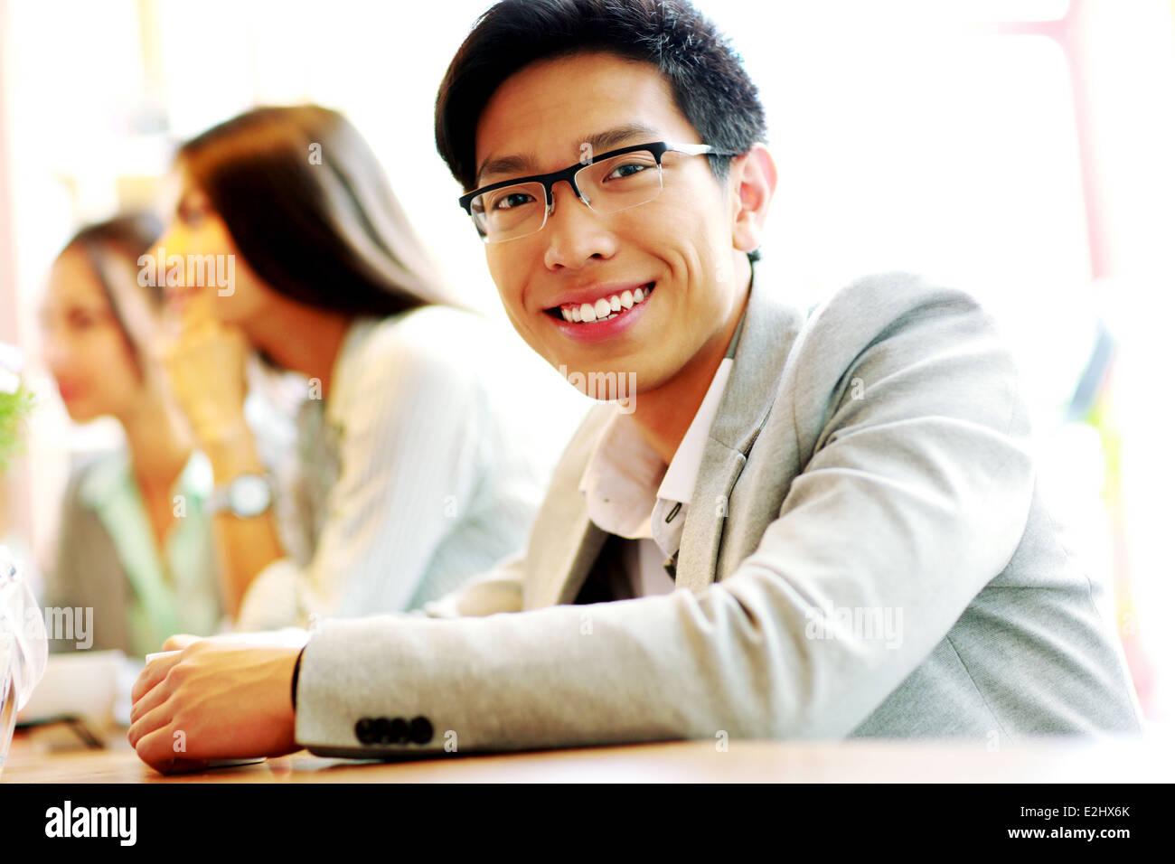 Portrait of smiling businessman assis devant des collègues Photo Stock